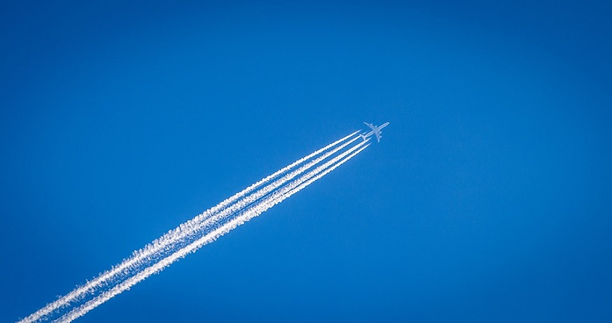 Airplane contrails - Airplane leaving trail in blue sky
