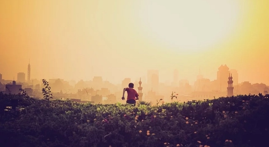 India air pollution - boy running toward smoggy city in India