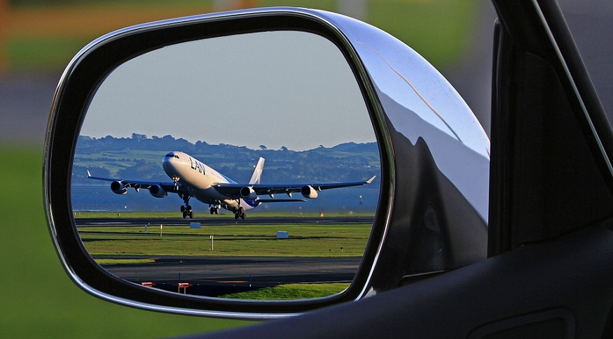Hydrogen planes - plane taking off seen from car side mirror