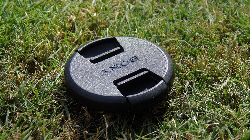 Renewable energy initiative - Sony camera lens cap on grass