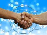 Blue hydrogen partnership - handshake- blue background